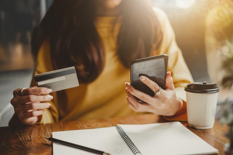スマホとクレジットカードを手に持つ女性