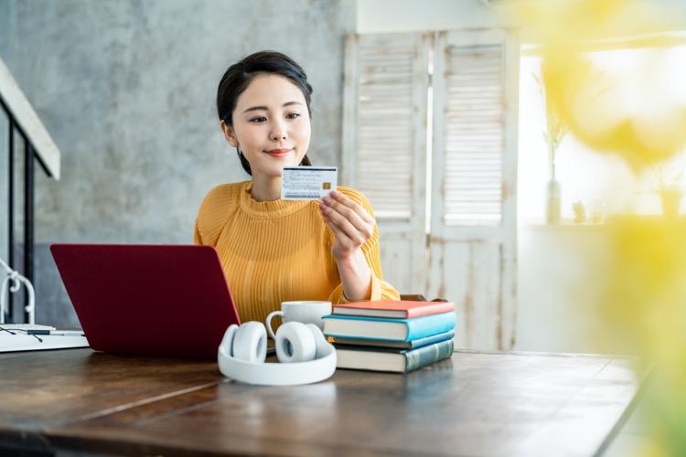 パソコンを前にクレジットカードを手に持つ女性